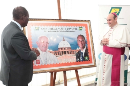 Alassane Ouattara and Apostolic Nuncio Paolo Borgia during the unveiling ceremony of the commemorative stamp of the 50th anniversary of the establishment of diplomatic relations between Ivory Coast and the Vatican.
