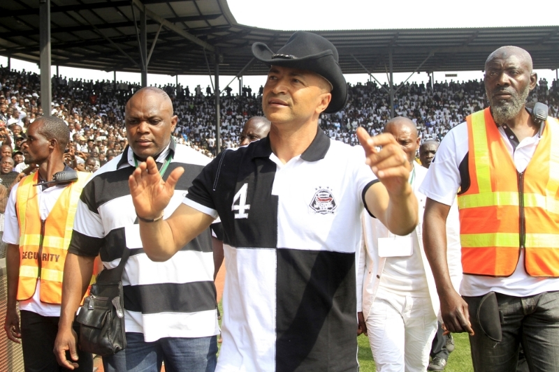 Moise Katumbi, wearing a TP Mazembe jersey, salutes supporters in the club stadium in Lubumbashi.